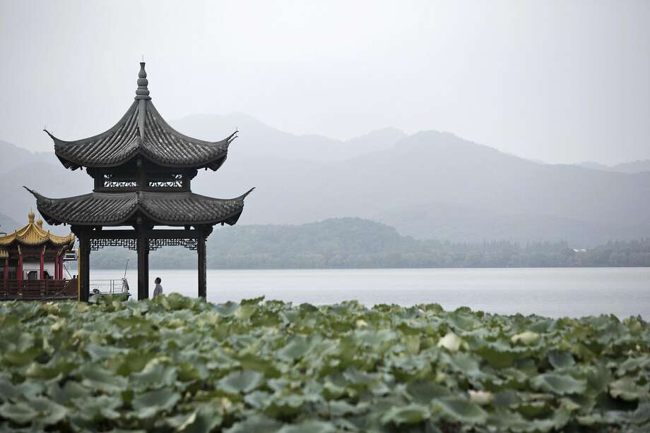 A man stands in a pavilion on the waterfront of the West Lake in Hangzhou, which was one of the eight ancient capitals of China. Photo: Qilai Shen, Bloomberg