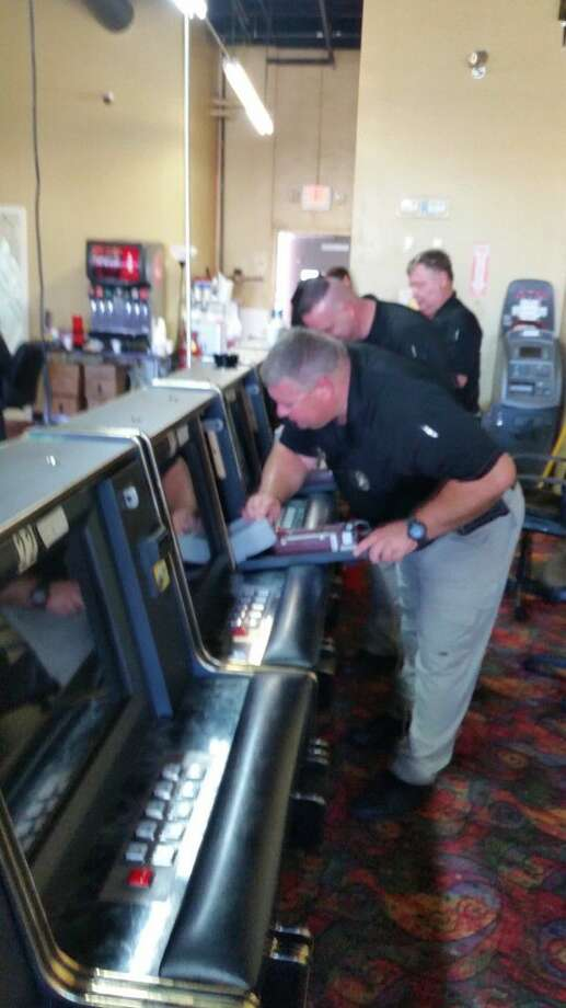 Detectives from the Fort Bend County Sheriff's Office remove money from a Richmond game room. The game room was shut down Thursday, and one employee was charged with gambling promotion