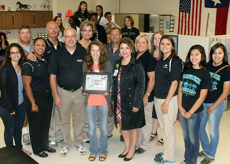 Memorial senior Elizabeth Burden (center) receives her scholarship certificate from Memorial Herman Southeast Representatives (flanking Burden) Bubba Wilson and Shannon Kimich. Also, in the front row, are senior Katelyn Perez; Roneka Lee, assistant athletics director for the Pasadena ISD; Trainer Stacy Havner; sophomore Lizette Mendoza; and junior Nancy Gomez. In the second row, are Chris Quillian, Memorial's athletics coordinator and head football coach; Pasadena ISD Head Trainer Randy Dugas; Memorial Principal Dr. Angela Stallings; Rodney Chant, director of athletics for the Pasadena ISD; Memorial Head Trainer Kathryn Vollmer; and Laura Shannon, Memorial's senior counselor.