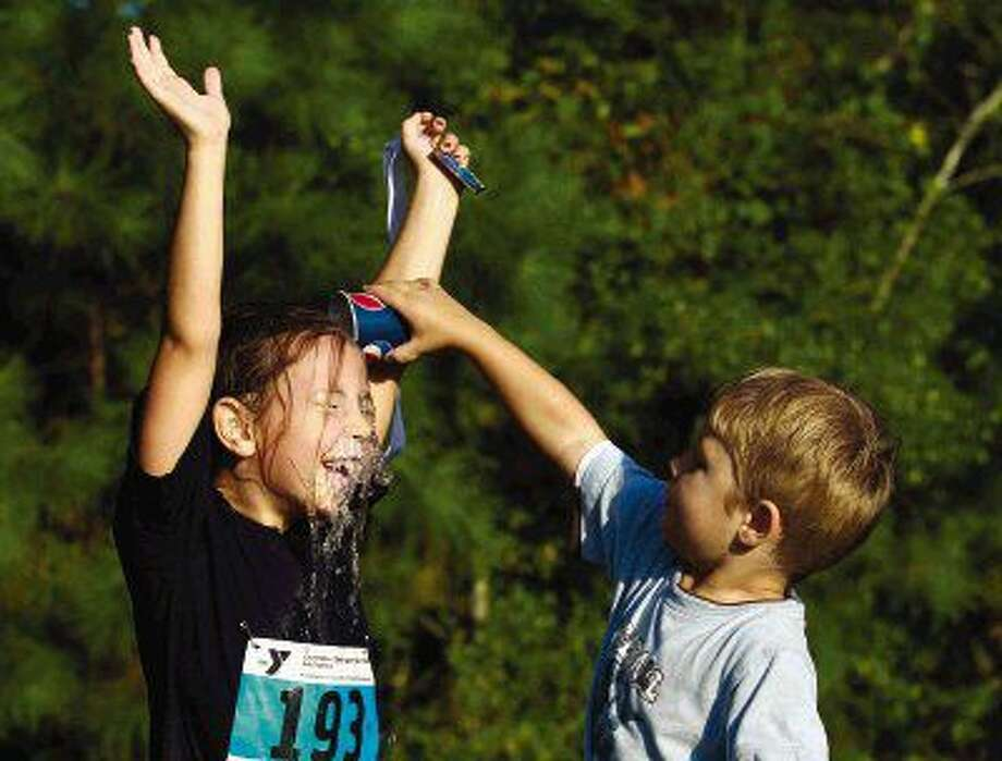 Bryn Hennefer is doused with water by her brother Jackson after competing in the YMCA Kids Triathlon Saturday in The Woodlands.