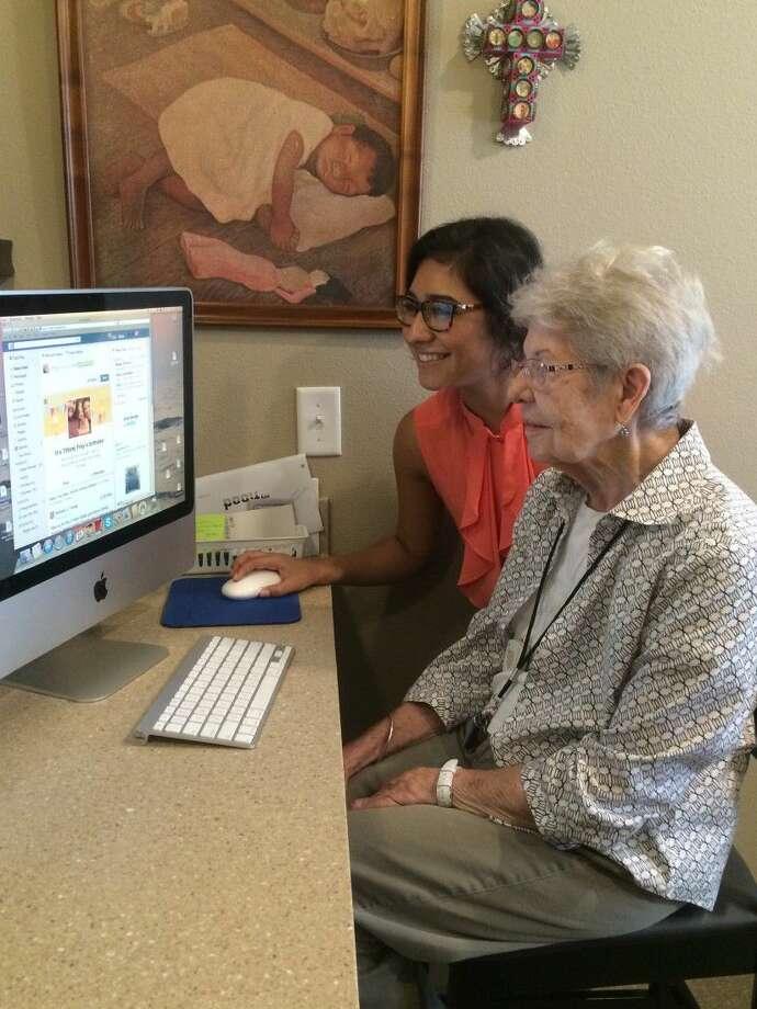 Avanti Senior Living intern, Taylor Deperri, helping resident, Betty Frey, with Facebook.
