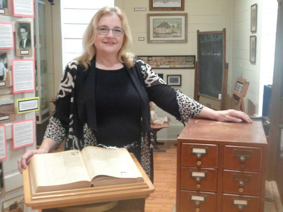 Paula Fielder, library coordinator for Dayton ISD, stands with an old oversized abridged dictionary that was used at Woodrow Wilson Junior High after 1962 and a small card catalog that was used at Colbert School prior to the computer automation of libraries. Both items were donated to the Old School Museum in Dayton. Photo: Submitted