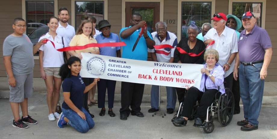 Courtney Lee (middle) cuts the ribbon for his business, Cleveland Back and Bodyworks on July 16 to commemorate joining the Greater Cleveland Chamber of Commerce. Photo: Jacob McAdams