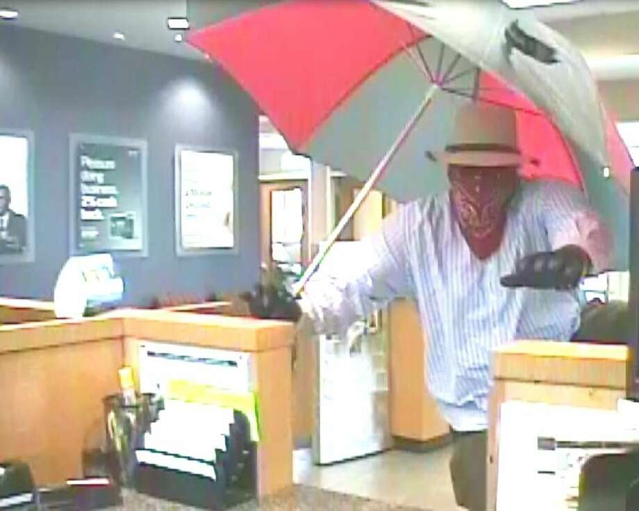 """On Thursday, July 21, Galveston Police Department were dispatched to Capital One Bank, 6229 Stewart Road, in reference to a robbery. Witnesses advised that a man walked into the store, jumped over the counter, and demanded money from employees. The suspect is described as a male, possibly black, 5'09"""" tall, and weighing 200-250 lbs. The suspect was wearing a hat, long sleeve shirt, pants, gloves, and a red bandana over his face. The suspect was also carrying a red and gray umbrella. No weapons were observed during the robbery. Galveston County Crime Stoppers is offering a 1,000 cash reward for information leading to the arrest of the person or persons responsible for this crime. You may submit a tip by calling 409-763-TIPS, or online at galveston.crimestoppersweb.com. Tipsters will remain anonymous. You may also contact Detective Gaspard with the Criminal Investigations Division at 409-765-3778. Photo: Courtesy Galveston Police"""