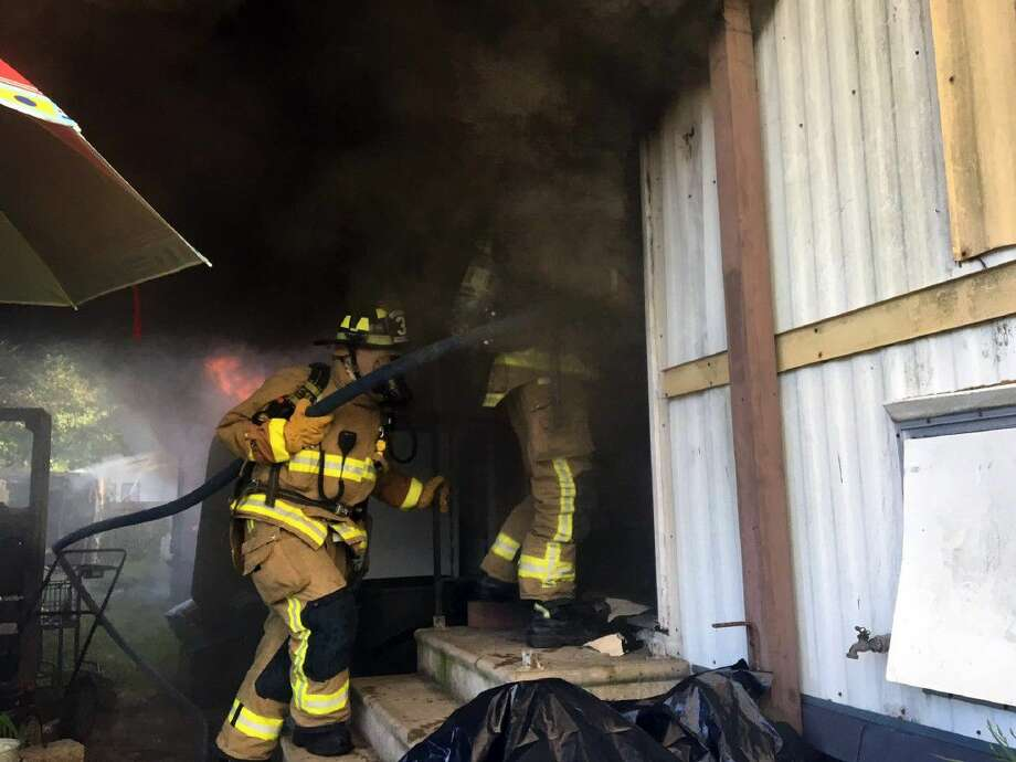 League City Volunteer Firefighters start an interior attack to stop the fire from spreading to the rest of the structure Photo: Eran Denzler