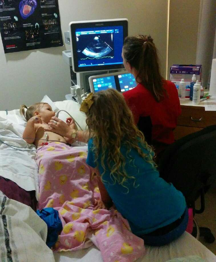 An ACC DCVS student performs a heart scan on a young volunteer.