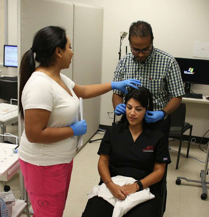 ACC Polysomnography graduate Elizabeth Gonzalez, left, shows Baylor College of Medicine Dr. Viral Kothari, how to prepare for a sleep study on ACC student Maricella Lopez on July 11.