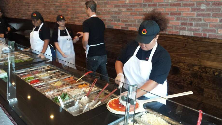 Persona Pizza employees make a pizza fresh during their soft opening Tuesday.