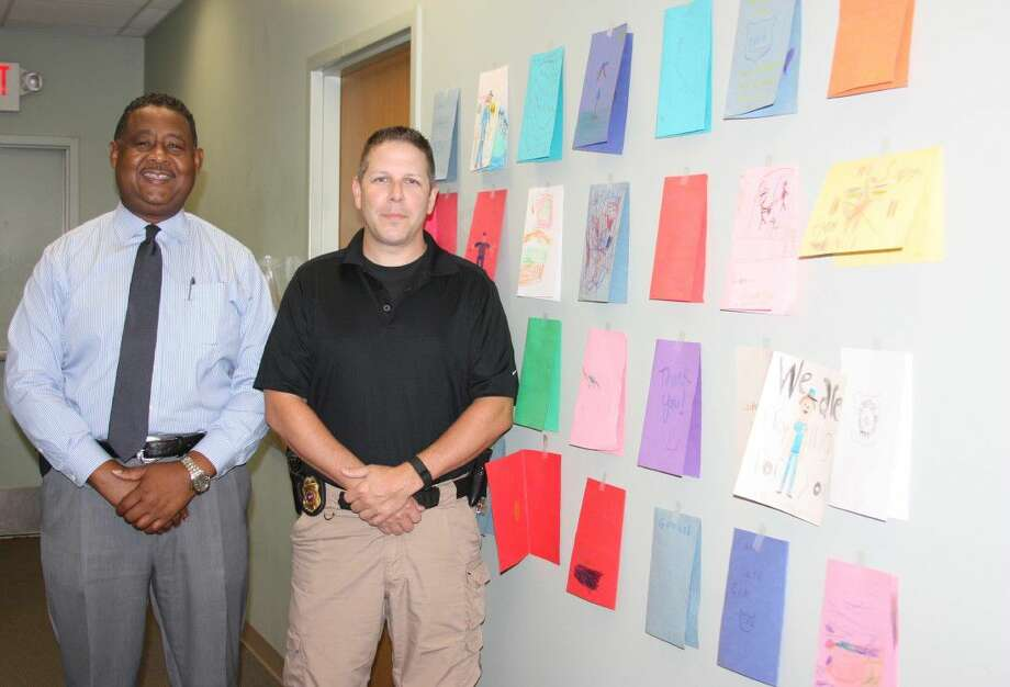 Cleveland Police Chief Darrel Broussard and Capt. Scott Felts stand beside a wall of letters they received from local children. The letters contain messages of support and to thank Cleveland police officers for their service to the community. Photo: Vanesa Brashier