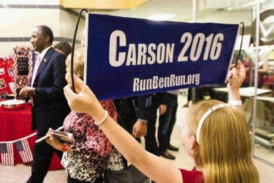 Peyton Easley holds up a sign in support of Republican presidential candidate Ben Carson during his visit to Conroe High School Thursday.