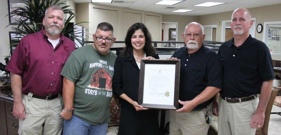 Michele Carfello (middle) presents a plaque to Denny Clark (second from right) and his sons for the Bank of San Jacinto County's service to the community during their open house event on July 27 in the bank's main lobby. Photo: Jacob McAdams