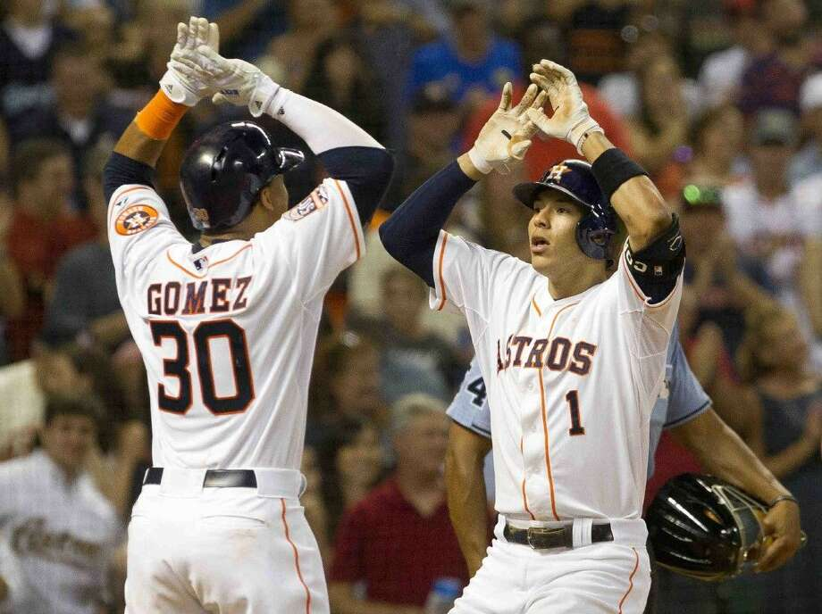 Houston Astros' Carlos Correa, right, celebrates with Carlos Gomez after hitting a two-run home run in the sixth inning of an MLB baseball game Saturday, August 1, 2015. Photo: Jason Fochtman