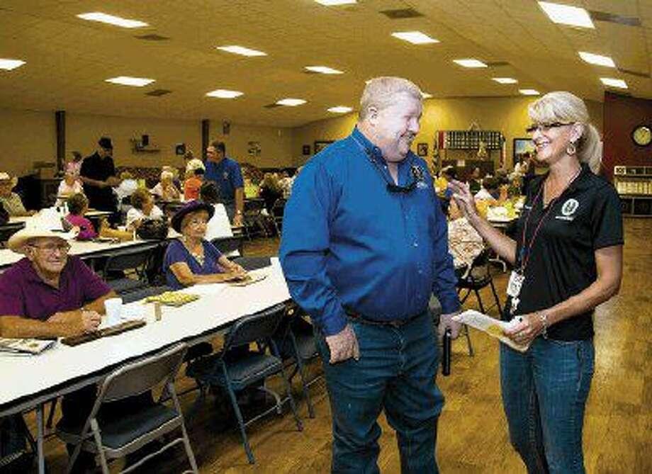 Montgomery County Precinct 4 County Commissioner Jim Clark talks with Rhonda Behnken, facility coordinator for the East Montgomery County Senior Center.