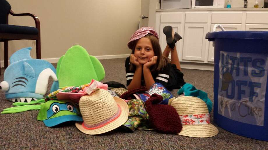 Kaitlyn Sitton poses with a few hats she's collected for Hats Off for a Cure.