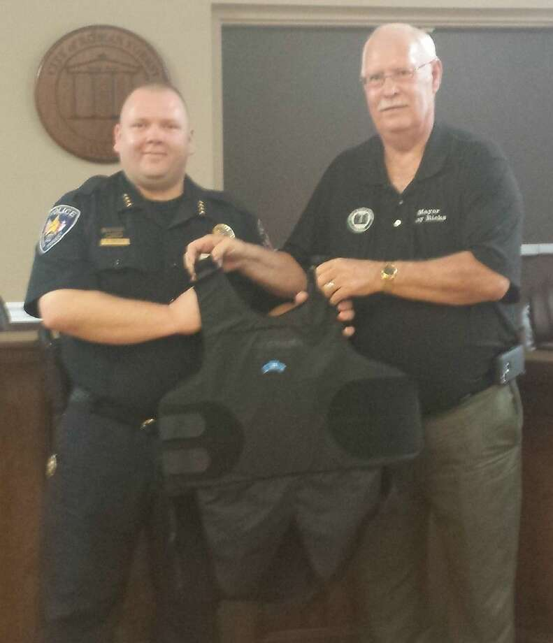 Roman Forest Mayor Ray Ricks (right) presents Roman Forest Police Chief Stephen Carlisle with one of 16 ballistic vests that were donated by the 100 Club.