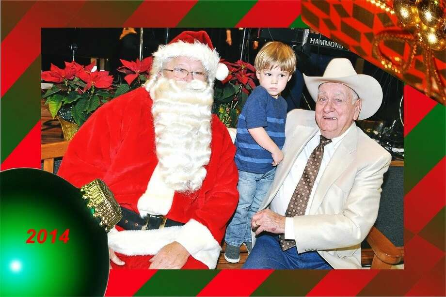 """Santa Claus, who bears a unique resemblance to HTO's Producer Dan Wester, extends Christmas cheer to Performer Arnold Parker and his grandson. A talented """"vintage"""" performer, Arnold pleased patrons with his presentation of """"Her Heart belongs to Texas,"""" """"I saw Mommy Kissing Santa Claus"""" and others."""