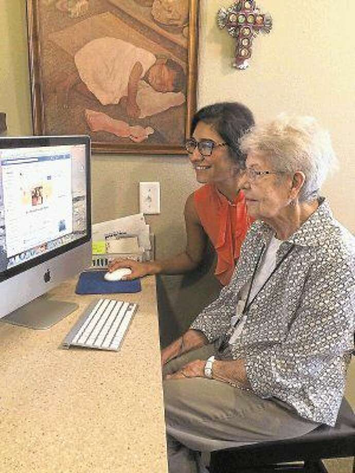 Avanti Senior Living intern Taylor Deperri helps resident Betty Frey with Facebook.