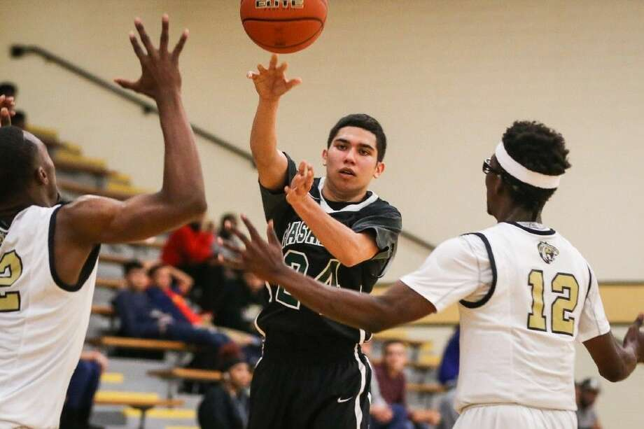 Pasadena's Josh Martinez splits the Conroe High School defense with a pass to a teammate during a Monday night game in Conroe. The contest acted as a tune-up for head coach Jason Pillow's club and their trip to the 82nd annual Krueger/Carlisle Classic. Martinez and the Eagles will be trying to upset favored Clear Lake when they tip off at 6 p.m. The Falcons have won the tournament over a dozen times in the school's 41-year history. Photo: Michael Minasi