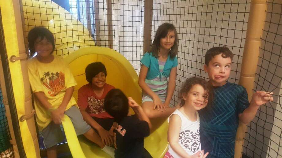 Children pose by the slide, and some make goofy faces, at the Kingwood United Methodist Church indoor playground Thursday, July 28.