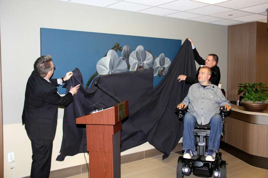 Carl Josehart, Senior Vice President and CEO, TIRR Memorial Hermann, (far left) helps unveil one of two paintings in the TIRR Memorial Hermann lobby painted by former patient Jared Dunten. Photo: Submitted Photo