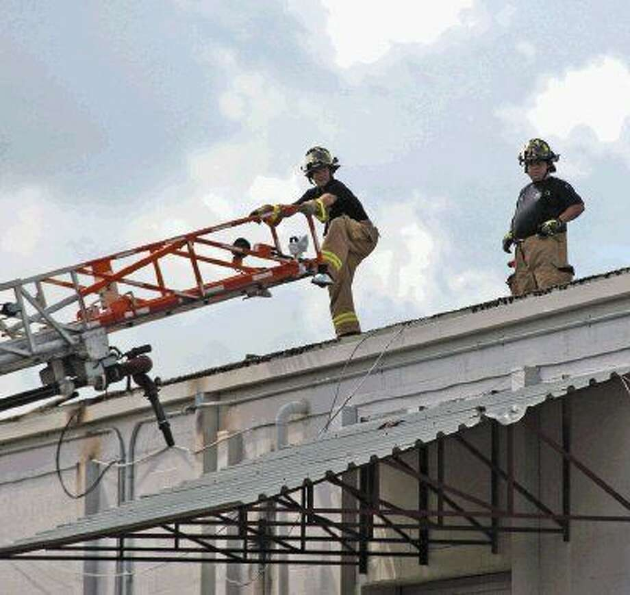 Houston Firefighters from station 71 prepare to descend the ladder after roof operations at a warehouse fire in the 900 block of Gemini in Webster October 1, 2014. Photo: Staff Photo Kar B Hlava