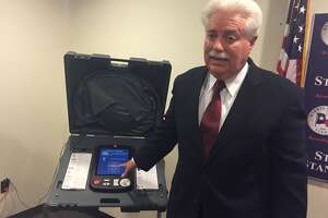 Harris County Clerk Stan Stanart exhibits a voting machine used in Harris County, which he said can't possibly be hacked because it isn't connected to the internet.