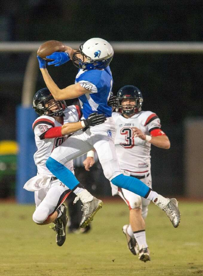 Episcopal senior wide receiver Cameron West goes high in the air over a St. John's defender to snatch one of his five catches Friday night during the Knights' 38-0 triumph over the Mavericks. The Knights host Kinkaid Thursday night in the annual game with first place in the South Zone on the line. Photo: Kevin B Long