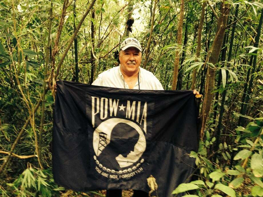 Vietnam veteran Peter Post the POW-MIA flag on Hill 700 before a memorial service for his fellow Marines during the 2014 investigative mission to Vietnam.