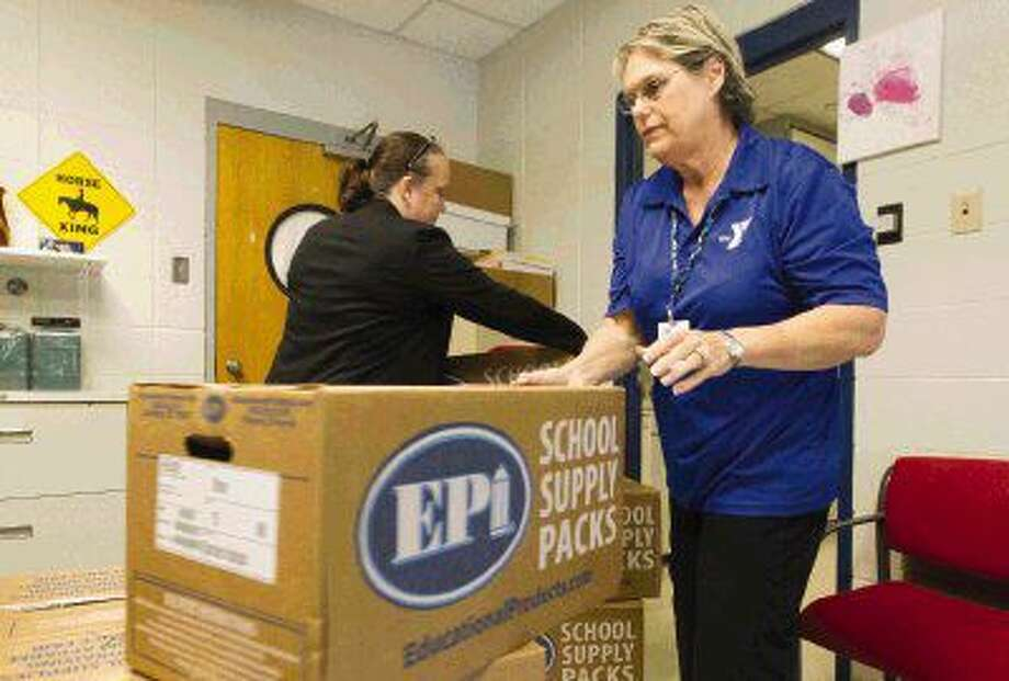 Terri Walters, right, and Pauline Veazey unload school supplies in support of Operation Backpack at the Conroe Family YMCA Tuesday in Conroe. Photo: Jason Fochtman