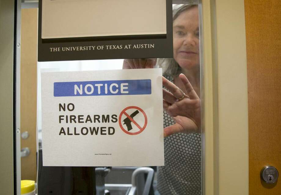 University of Texas at Austin Anthropology professor Pauline Strong posts a sign prohibiting guns at her office on the first day of the new campus-carry law Monday.
