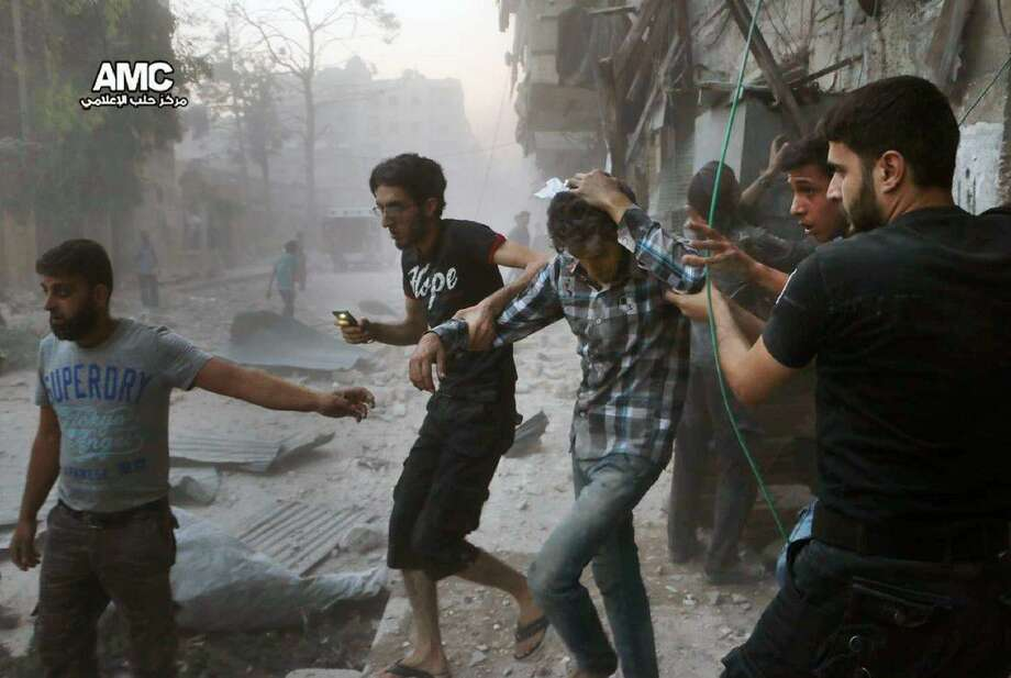 Syrians help an injured man, center, after airstrikes hit Aleppo, Syria, Sunday.