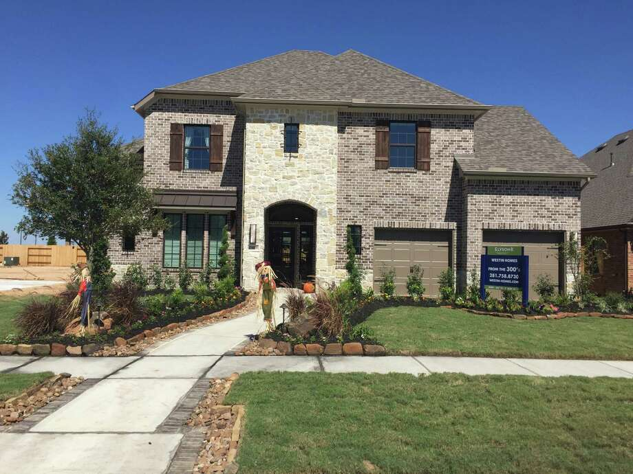 Models include the Preston III by Westin Homes, which has a rotunda foyer, highlighted by a spiral staircase with wrought-iron spindles.