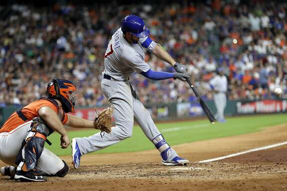Chicago Cubs' Kris Bryant (17) hits a two-run home run as Houston Astros catcher Evan Gattis reaches for the pitch during the fifth inning of a baseball game Friday, Sept. 9, 2016, in Houston. (AP Photo/David J. Phillip)