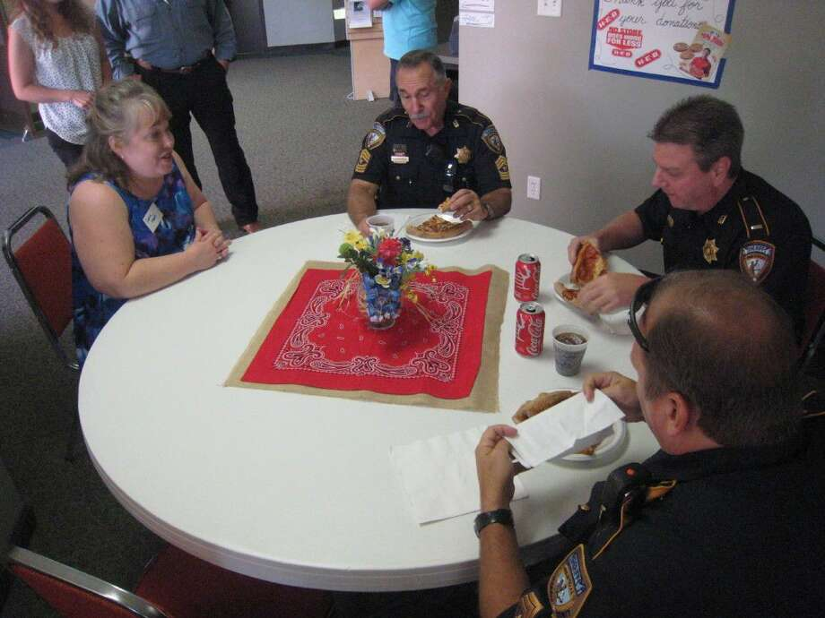 Several law enforcement officers of the Harris County Sheriff's Office enjoy pizza and fellowship with a Kingwood Bible Church member Wednesday, Aug. 3, 2016.