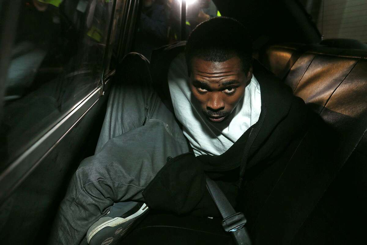 Olice Brown, 28, sits in a patrol car after he was escorted out of the San Antonio Police Headquarters to be booked in 2014. Brown was sentenced Wednesday to 60 years in prison for killing Cornell Glover, Sr., 38 and his son, Cornell Glover, Jr., 19.