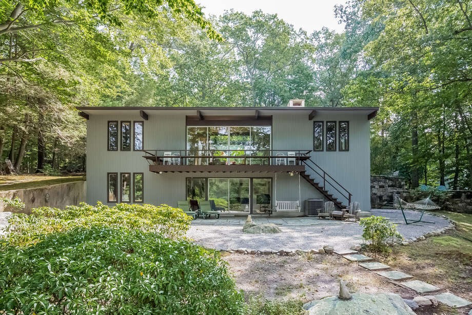 The glass-covered back of the midcentury modern home in North Stamford, which is on the market for $1.3 million. Photo: Contributed Photo / Phyllis Doonan & Associates