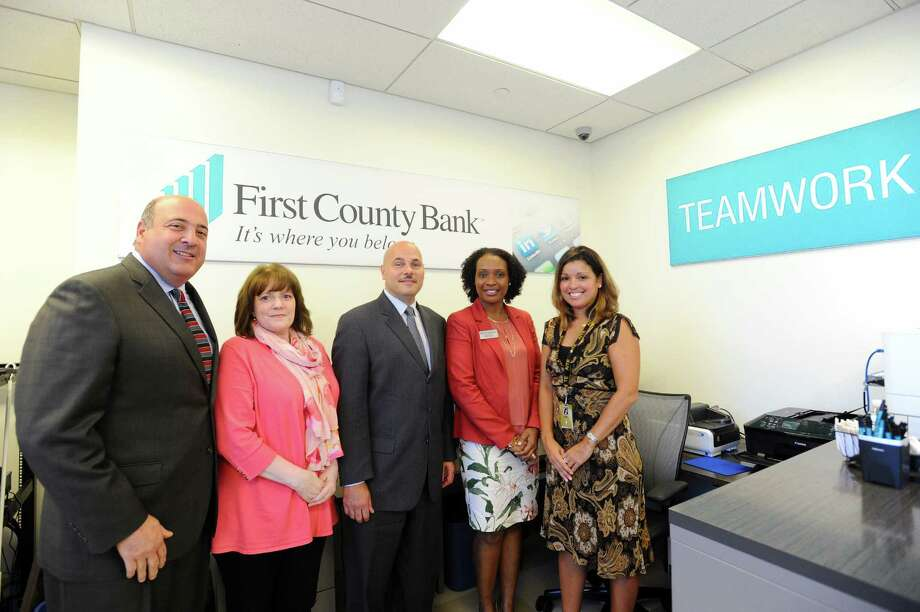 From left, First County Bank president and COO Bob Granata, First County Bank VP Sandy Holbrook, First County Bank senior VP Willard Miley, branch manager Sheila Content and AITE principal Tina Rivera pose inside AITE's new First County Bank limited-access branch in Stamford, Conn. on Wednesday, Oct. 5, 2016. Photo: Michael Cummo / Hearst Connecticut Media / Stamford Advocate