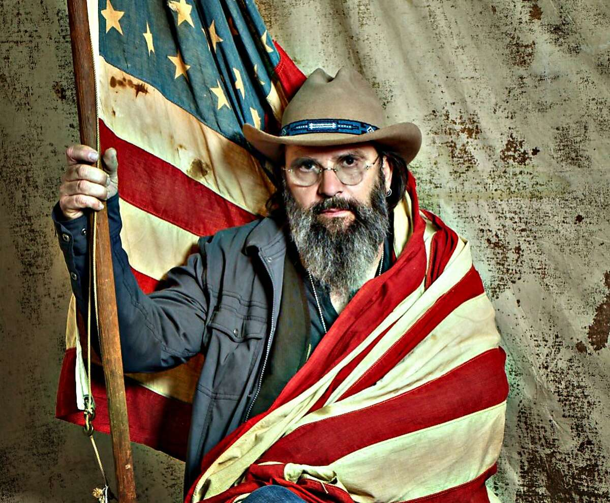 """Photographer Olivia Hellman's """"The 100% Genuine, Ltd. Edition, Absolutely Bonafide, Traveling Portrait Tent"""" is a backstage space at Hardly Strictly Bluegrass that she fills with whimsical, old-timey props to inspire creative poses among the festival artists she shoots. Pictured is Steve Earle."""