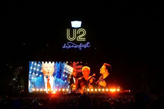 U2 lead singer Bono conducts a mock debate with a video image of Republican Presidential candidate Donald Trump on the main stage during the Concert for the Kids at the Cow Palace. Oct. 2016.