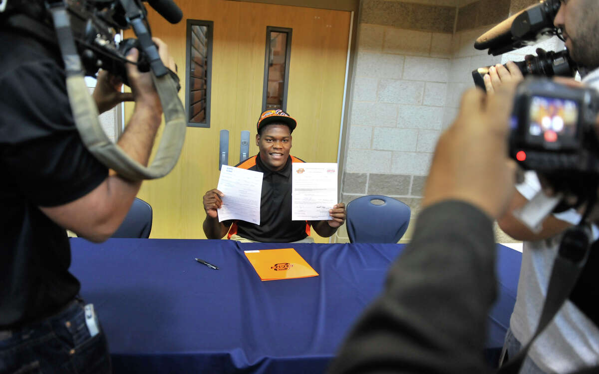 Madison's Vincent Taylor shows off his signed football scholarship to Oklahoma State in 2013.