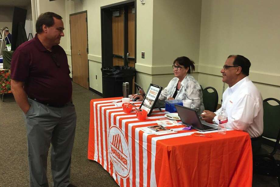 Encouraging them to build in Dayton, Courtland Holman, executive director of the Dayton Community Development Corporation (at left) visits with Whataburger's Traci Henson, regional recruiting manager, and Samir Moawad, area manager, during the City of Dayton job fair on Thursday, Aug. 4. Photo: Casey Stinnett