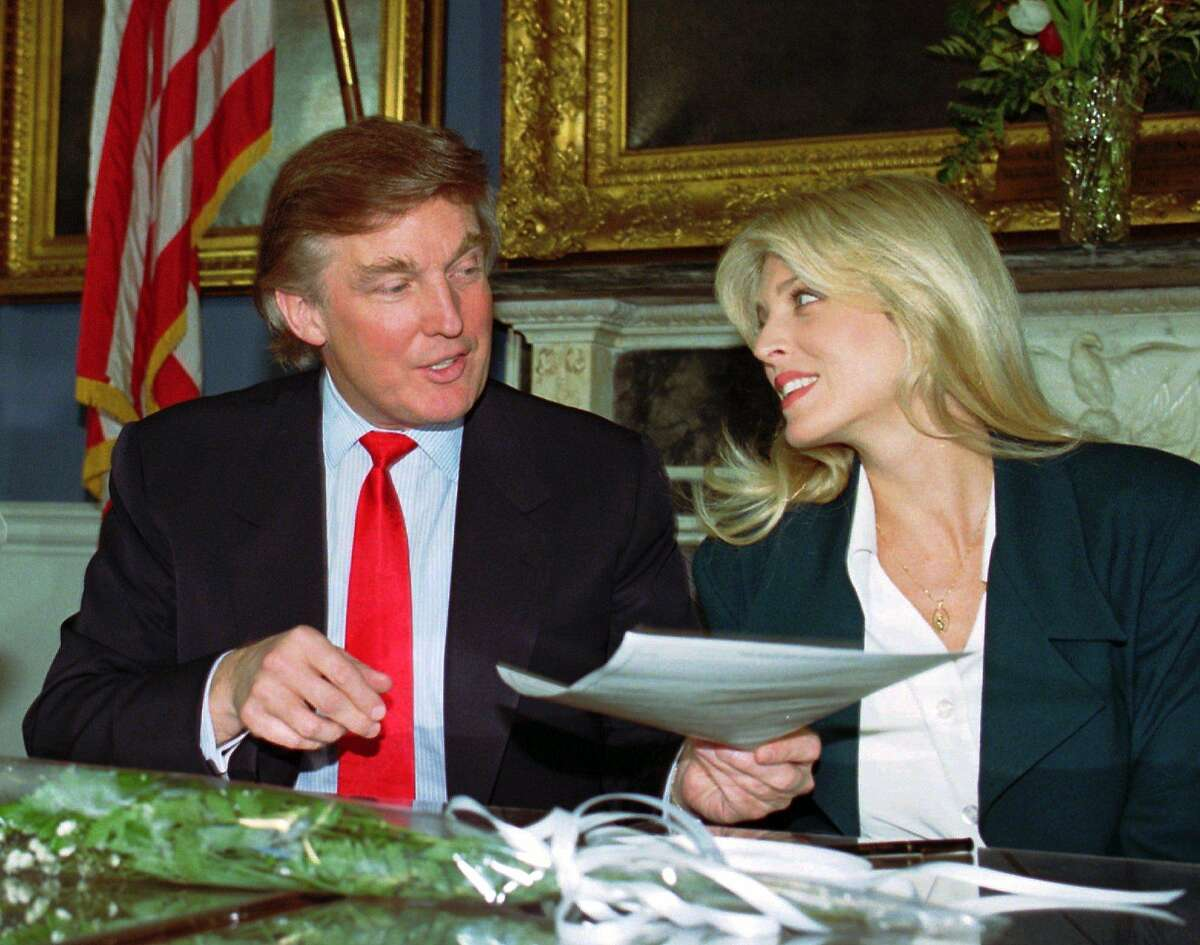 CHRONICLE 12/18/93 // Marla Maples eyes fiance Donald Trump as he holds the wedding license following their signing in the presence of New York City Mayor David Dinkins at City Hall in New York Friday, Dec. 17, 1993.