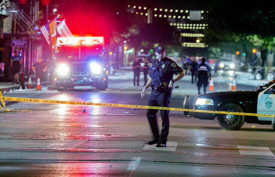 Police work the scene after gunshots rang out in downtown Austin, Texas, just as the bars were emptying early Sunday leaving one woman dead and several others wounded, and police searching for a suspect.