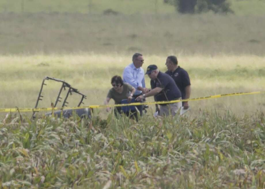 """The partial frame of a hot air balloon is visible above a crop field as investigators comb the wreckage of a crash Saturday in Central Texas near Lockhart, Texas. Authorities say the accident caused a """"significant loss of life."""" Photo: Ralph Barrera"""