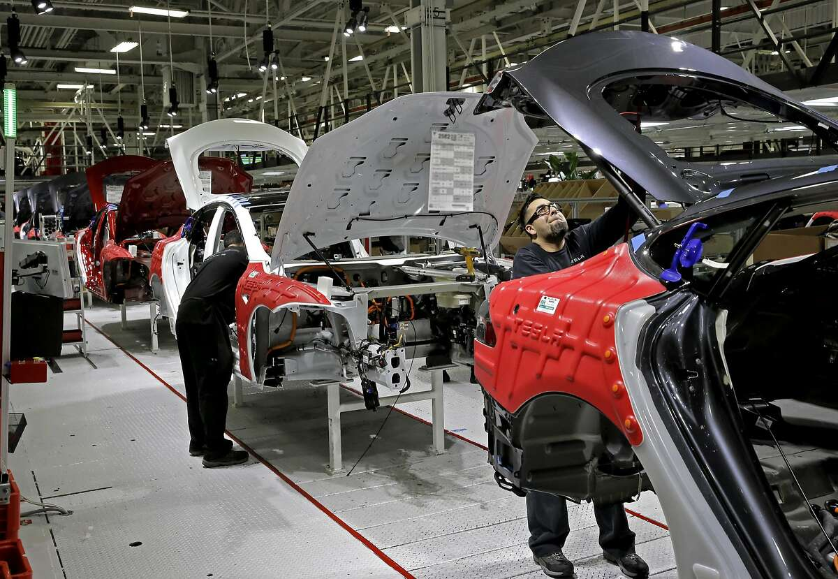 Workers along the assembly line at Tesla Motors, California's only full-scale auto manufacturing plant, as seen on Thurs. Feb. 19, 2015, in Fremont, Calif. NOTE: Certain areas of this image were blurred for security reasons.