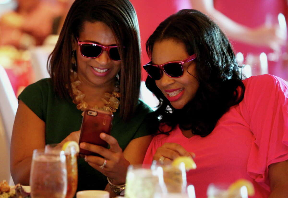 Tam Lagroce, left, and Tammara McDonald look at a selfie they took at the Razzle Dazzle Luncheon at the Westin Houston Memorial City Thursday, Oct. 6, 2016, in Houston.