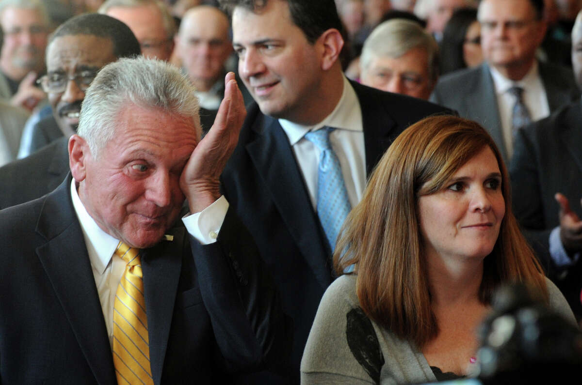Norwalk Mayor Harry Rilling, seen here with his daughter Christine Limone, wipes an eye after being sworn in to office in 2013 at Norwalk City Hall.