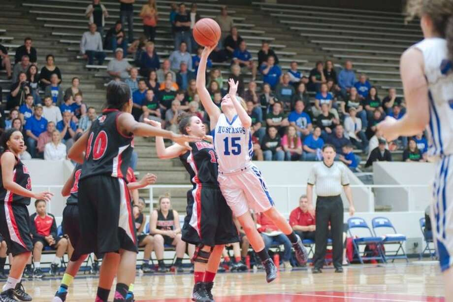 Friendswood's Abby McClure (15) drives to the basket against Goose Creek Memorial Tuesday night. The Lady Mustangs won 61-48 to advance to the regional tournament. Photo: KIRK SIDES