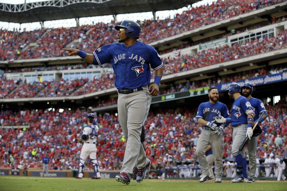 Toronto's Edwin Encarnacion points to Troy Tulowitzki after scoring on Encarnacion's bases-loaded triple in the third. Photo: LM Otero, Associated Press