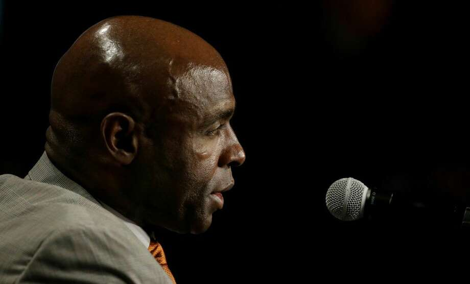 Texas head coach Charlie Strong arrives to speak to reporters during the Big 12 college football media days in Dallas.